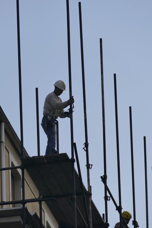 Arbetare i material till byggnadsställning för beslag för konstruktionsplats arkivfoto