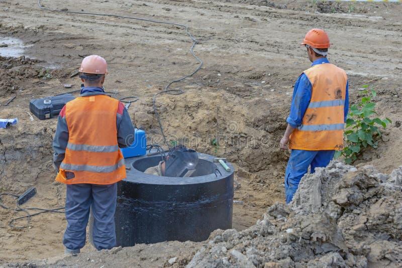 Arbetare i orange likformig på konstruktionsplatsen royaltyfri foto