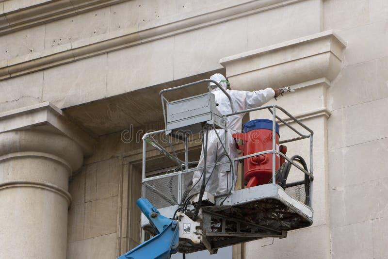 Arbetare i plattformen som tvättar en byggnad fotografering för bildbyråer