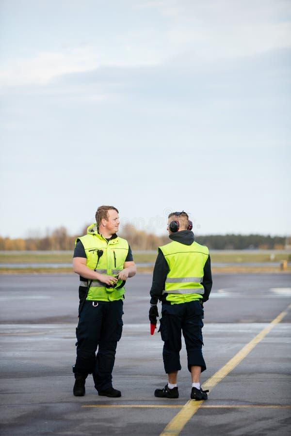 Arbetare i reflekterande omslag som står på flygplatslandningsbana royaltyfria foton