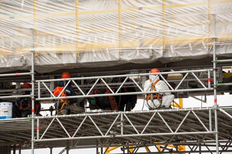 Arbetare i vita skyddande enhetliga fixanderör arkivbilder