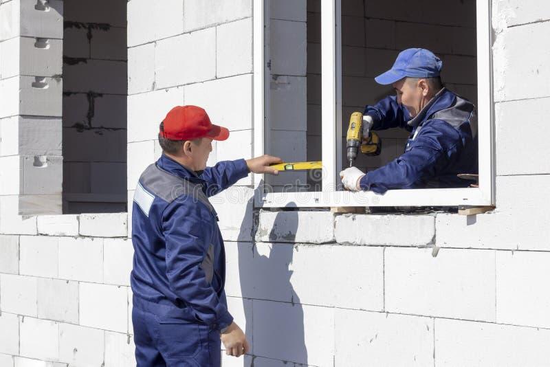 Arbetare installerar fönsterrutor i ett hus under konstruktion arkivfoto