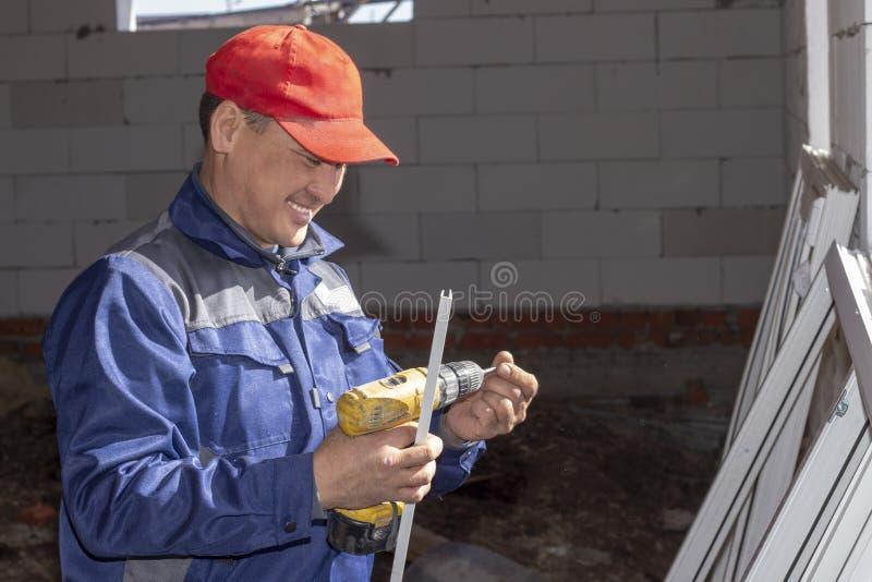 Arbetare installerar f?nsterrutor i ett hus under konstruktion arkivfoto