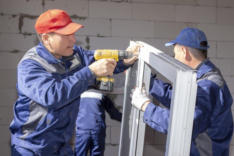 Arbetare installerar f?nsterrutor i ett hus under konstruktion fotografering för bildbyråer