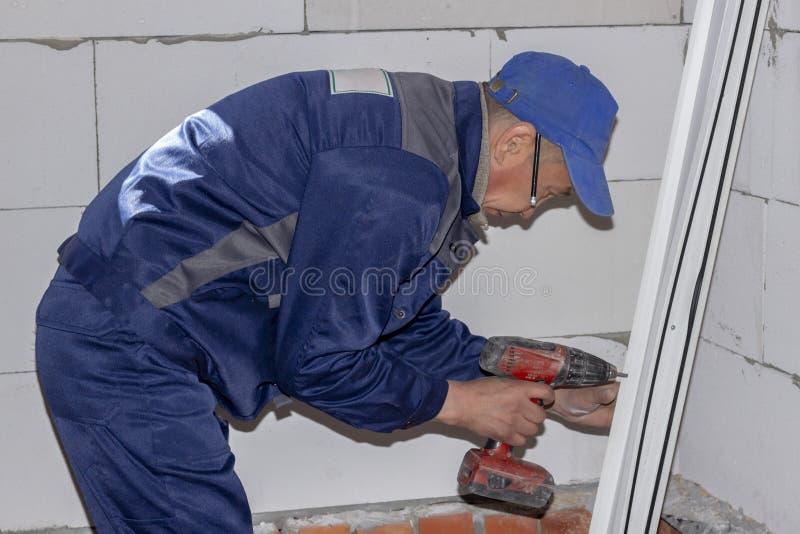 Arbetare installerar plast- reparation för hem- byggande för fönster arkivfoto