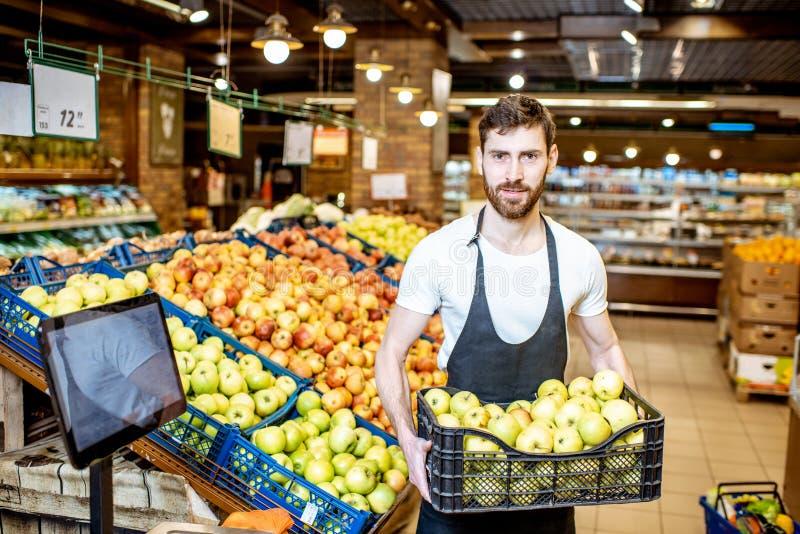 Arbetare med äpplen i supermarket fotografering för bildbyråer