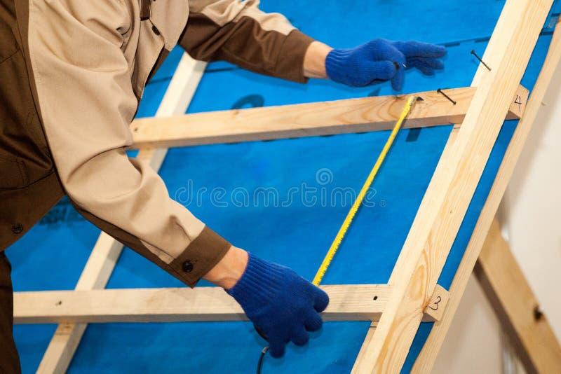Arbetare med den elektriska drillborren som installerar den bruna takmetalltegelplattan på trähus royaltyfri foto