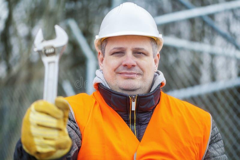 Arbetare med den justerbara skiftnyckeln på utomhus royaltyfri fotografi