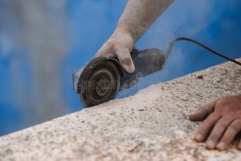 Arbetare med den radiella sågen med damm på luften med blå bakgrund royaltyfri bild