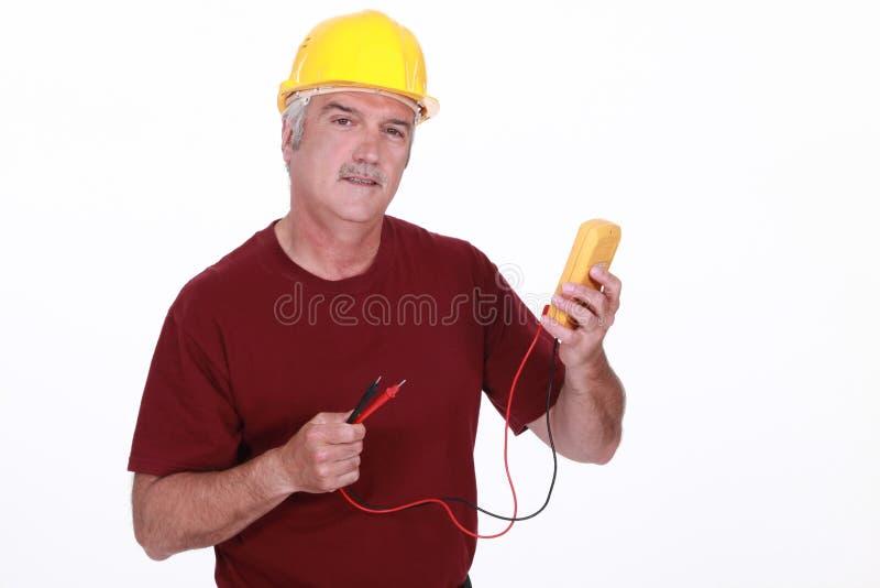 Arbetare med en voltmeter royaltyfri bild
