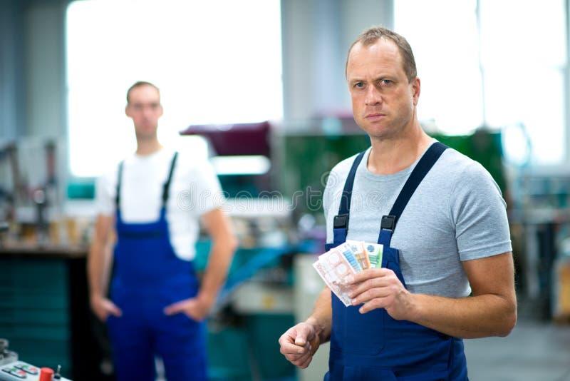 Arbetare med hans timpenningar royaltyfri foto