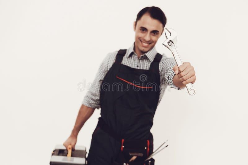 Arbetare med hjälpmedel och skiftnyckeln på vit bakgrund royaltyfri fotografi