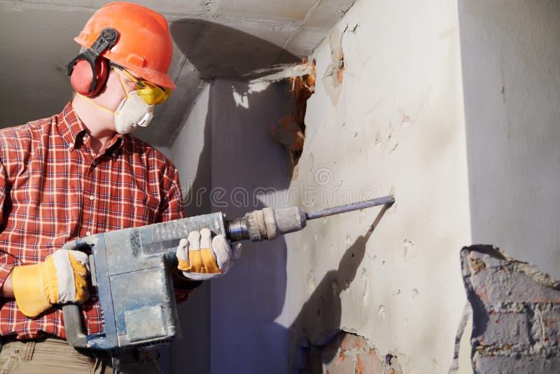 Arbetare med rivninghammaren som bryter innerväggen arkivfoton
