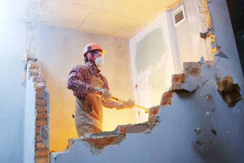 Arbetare med släggan på inomhus väggförstörelse royaltyfria foton