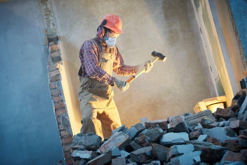Arbetare med släggan på inomhus väggförstörelse arkivbilder