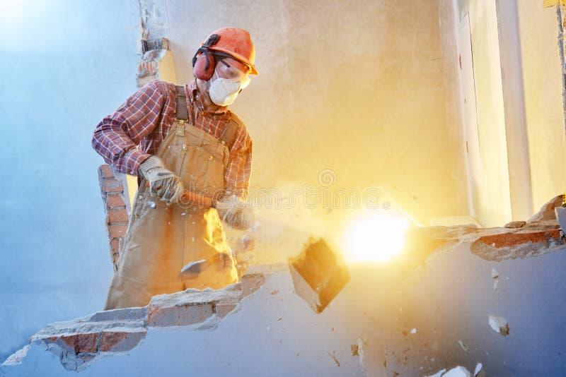 Arbetare med släggan på inomhus väggförstörelse royaltyfri foto