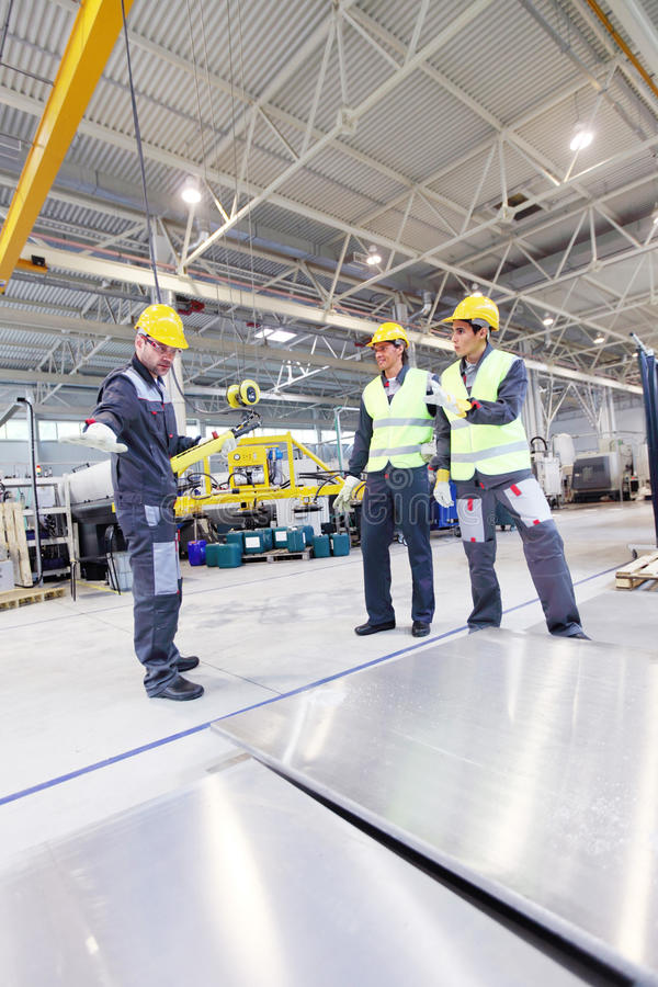Arbetare nära aluminium kubbar arkivbilder
