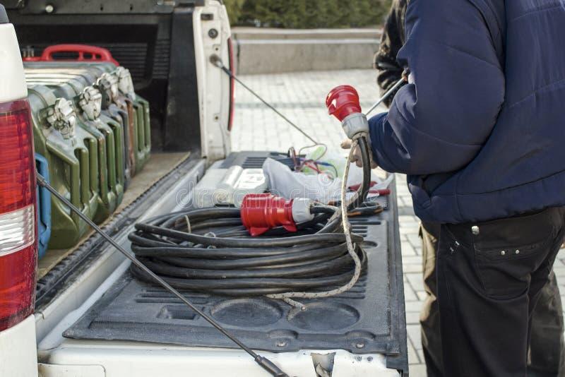 Arbetare nära bilen med den elektriska proppen för maktextander för byggnation med röda håligheter i hans händer royaltyfria bilder