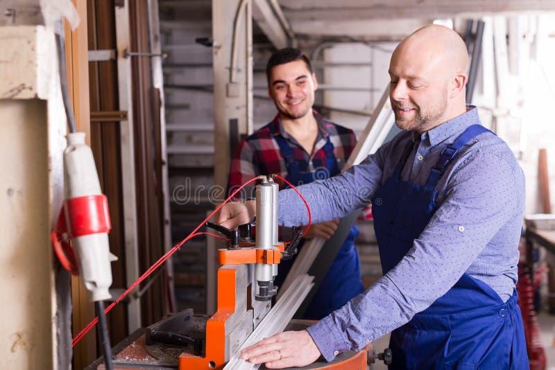 Arbetare near malningmaskinen royaltyfria bilder