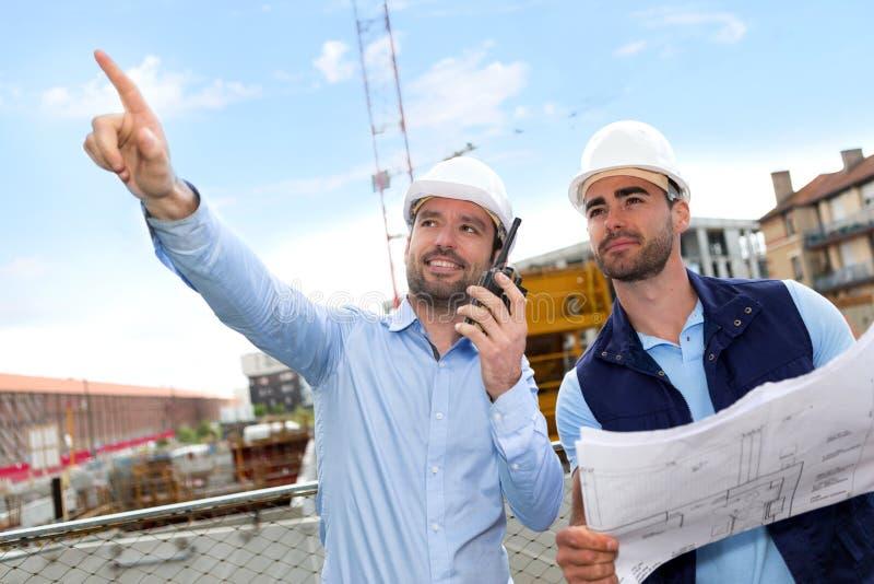 Arbetare och arkitekt som håller ögonen på några detaljer på en konstruktion fotografering för bildbyråer