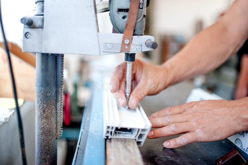 Arbetare och faktotum som använder ett industriellt hjälpmedel för att skruva fotografering för bildbyråer