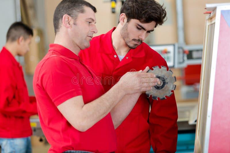 Arbetare och lärling i metallfabrik arkivfoto