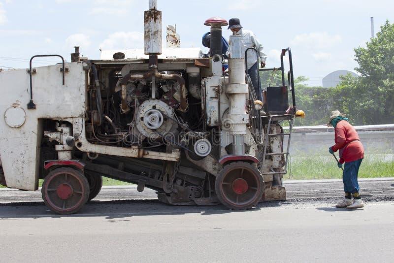 Arbetare och maskin som arbetar på vägkonstruktion royaltyfri foto