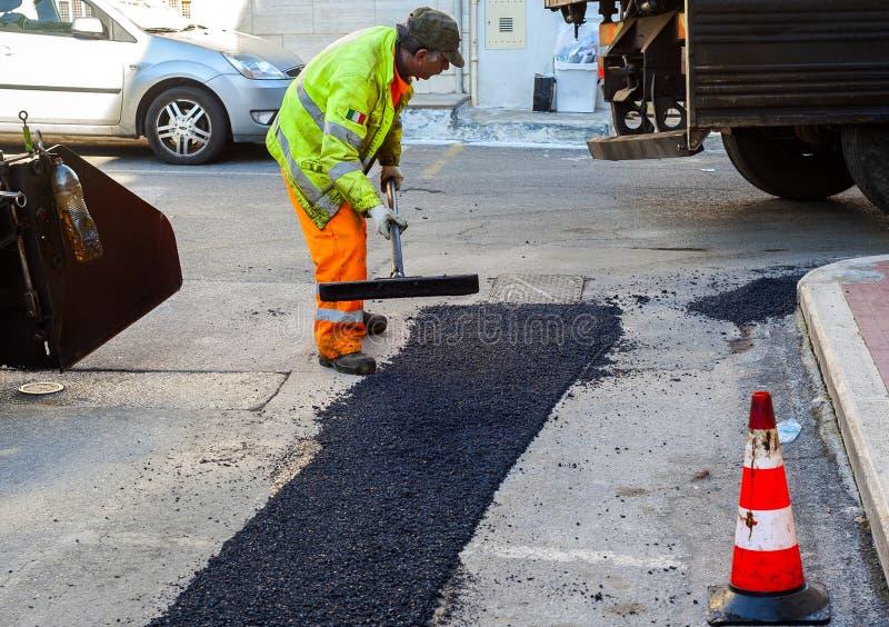 Arbetare på att asfaltera pavermaskinen arkivfoton