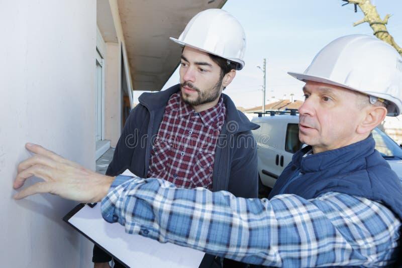 Arbetare på att rappa fasadarbete arkivfoto