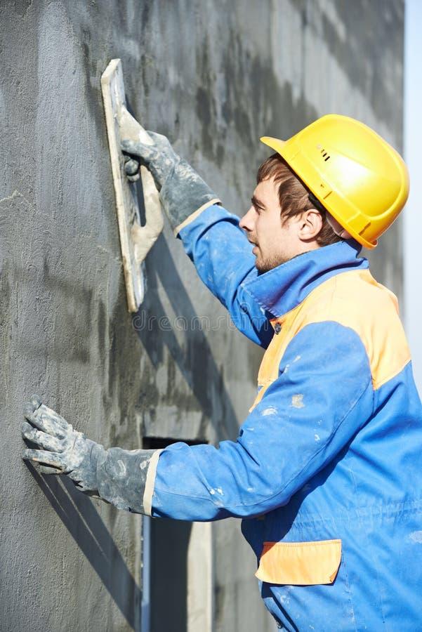 Arbetare på att rappa fasadarbete arkivfoton