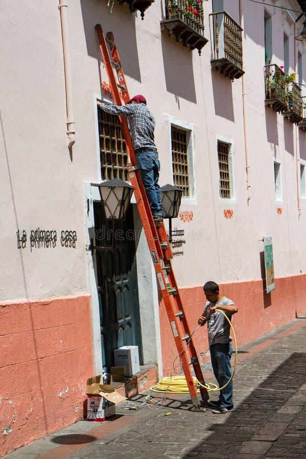 Arbetare på en stege fixar ett fönster i Calle La Ronda, typisk kolonial gata i det historiska området, Quito, Ecuador arkivfoton