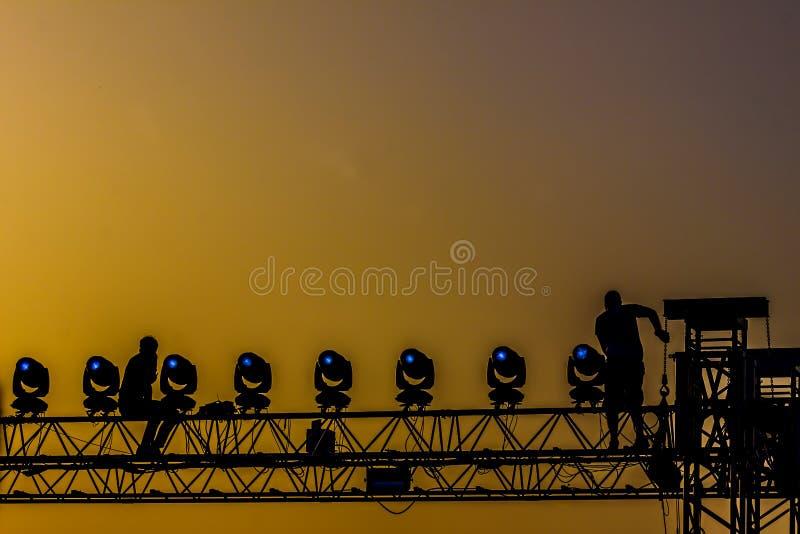 Arbetare på konsertstrukturen i solnedgången backlight royaltyfria foton