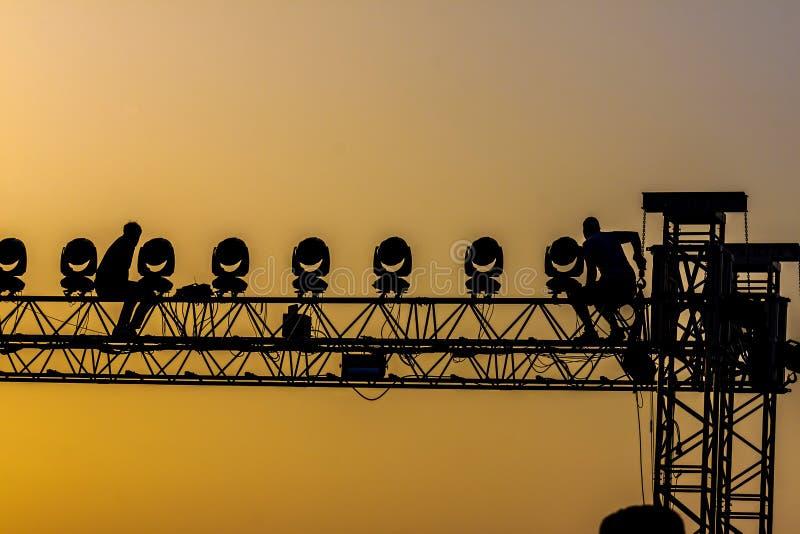 Arbetare på konsertstrukturen i solnedgången backlight royaltyfri fotografi