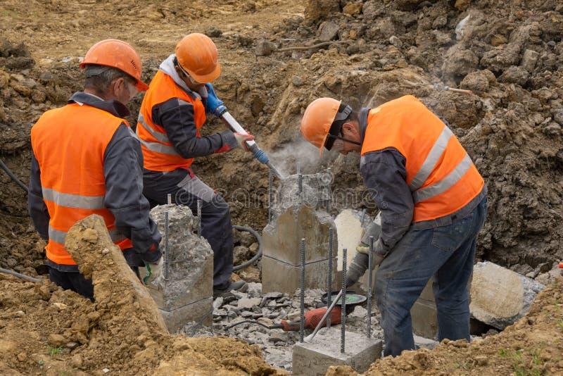 Arbetare på kotletten för konstruktionsplats som en tryckluftsborr traver klipps royaltyfria bilder