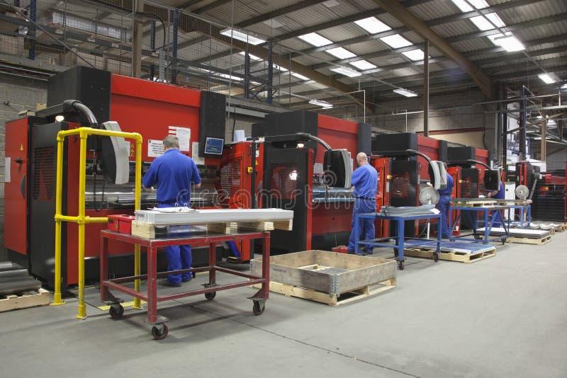 Arbetare på maskiner för tillverkningseminariumfungerings arkivfoton
