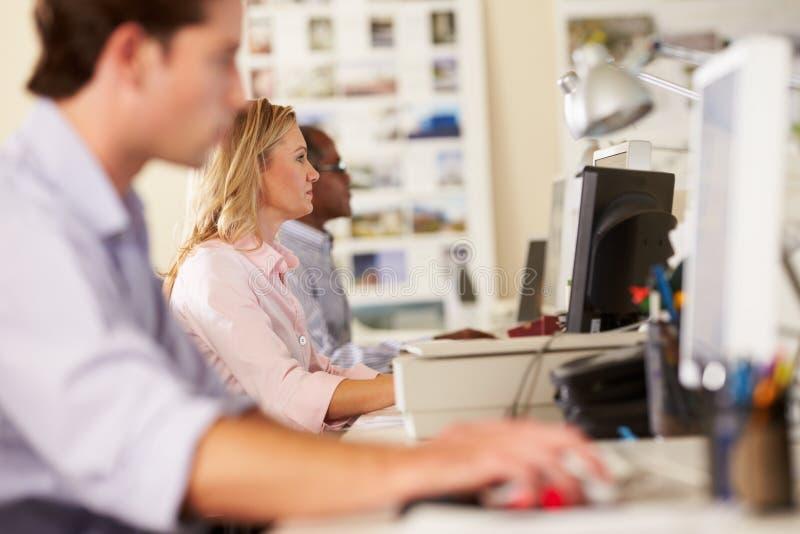 Arbetare på skrivbord i upptaget idérikt kontor royaltyfri bild