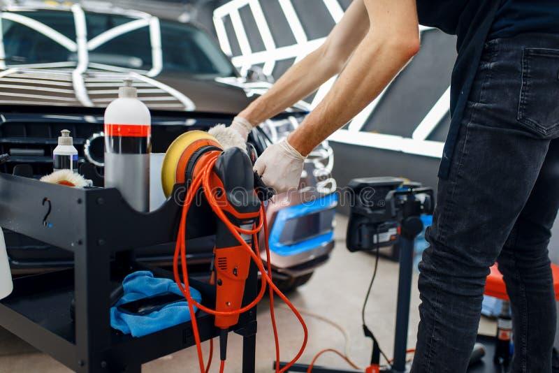 Arbetare, poleringsmaskiner och verktyg, detaljinformation om bilar royaltyfri foto