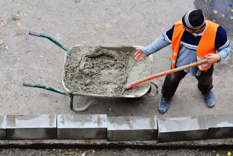 Arbetare skyfflar våt betong från skottkärran royaltyfria bilder