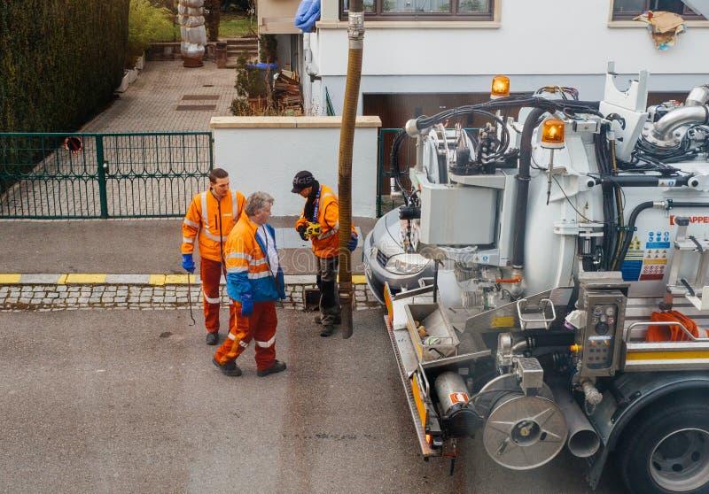 Arbetare som använder avloppsnätlastbilen och det stora röret som arbetar på cloggen arkivfoto