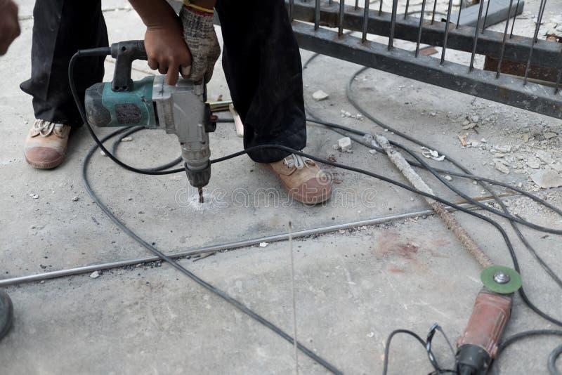 Arbetare som använder borrande för jordning för elektrisk drillborr vid maskinhjälpmedlet fotografering för bildbyråer