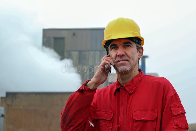 Arbetare som använder den smarta telefonen med fabriken i bakgrunden royaltyfri bild