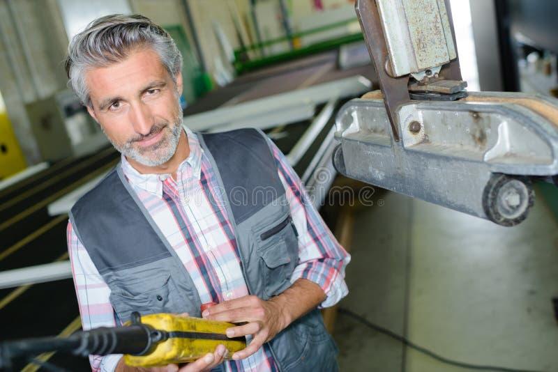 Arbetare som använder hängekontrollknappar i fabrik royaltyfria foton