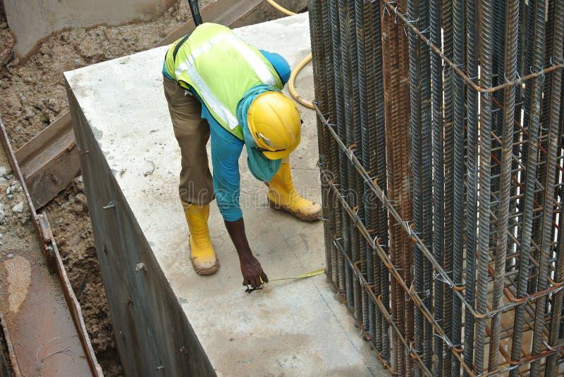Arbetare som använder mäta bandet på konstruktionsplatsen arkivbilder