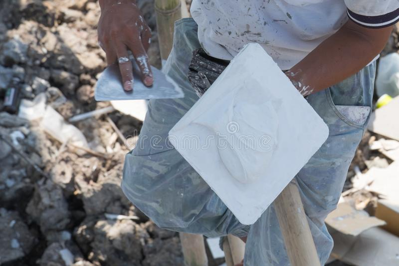 Arbetare som applicerar mursleven och rappar utrustning av att renovera huset royaltyfria foton