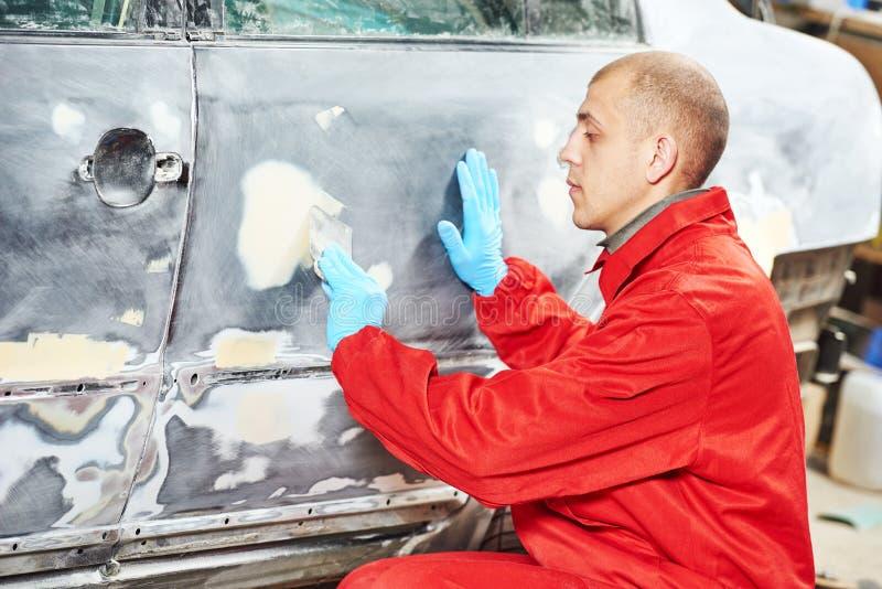 Arbetare som applicerar spackel för reparation för bilkropp royaltyfri bild