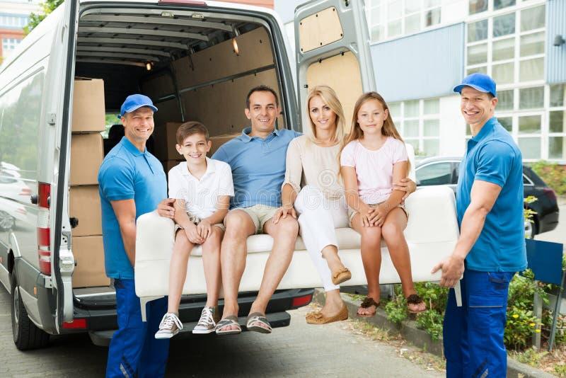 Arbetare som bär familjen med soffan royaltyfri fotografi