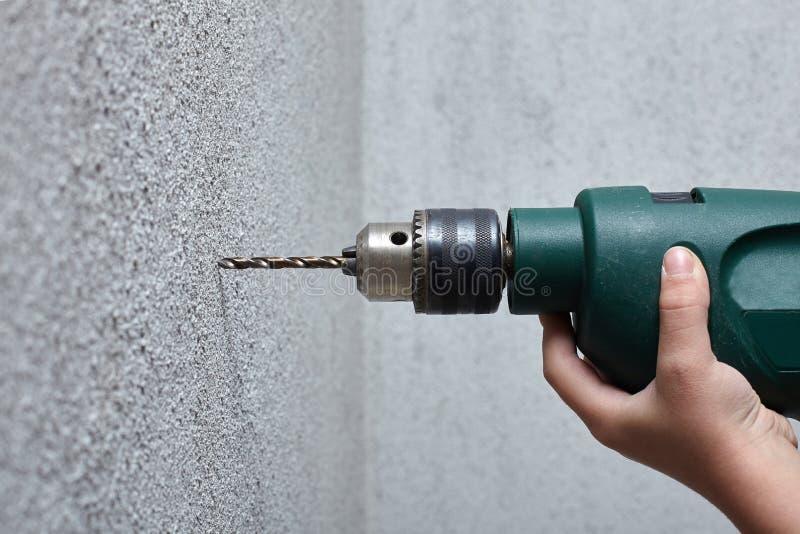 Arbetare som borrar ett hål in i väggen med en elektrisk drillborr royaltyfri bild
