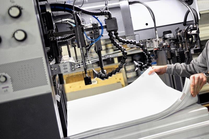 Arbetare som förbereder legitimationshandlingar för tryck på maskinen royaltyfri fotografi