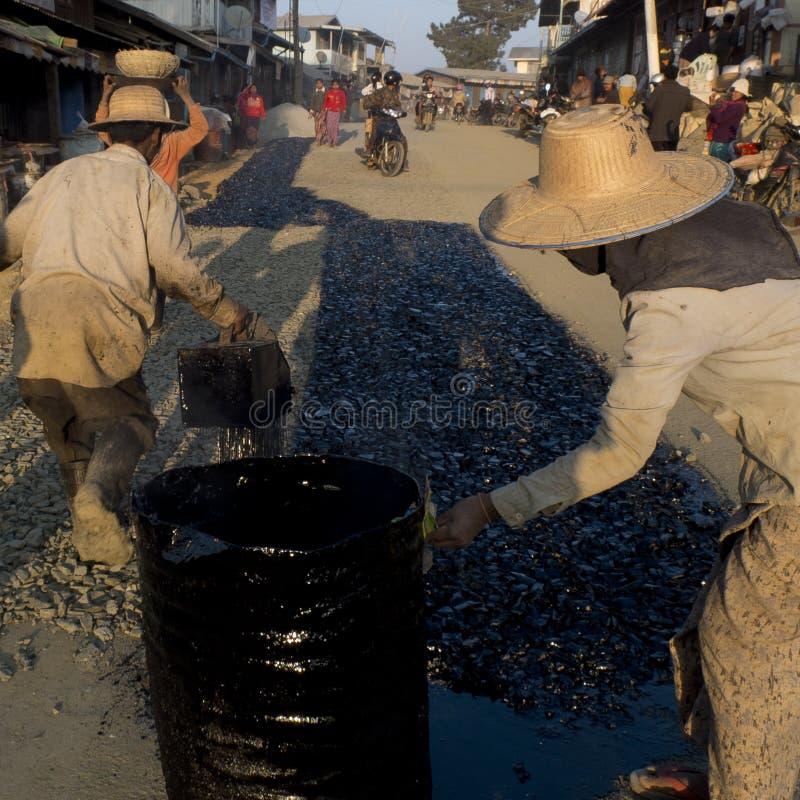 Arbetare som fördelar varm tjära på gatan arkivbild