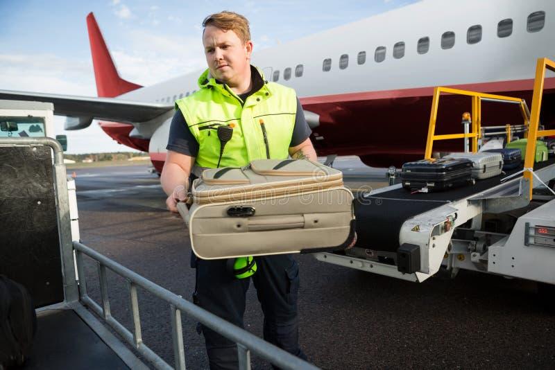 Arbetare som förlägger bagage i släp mot flygplanet arkivfoto